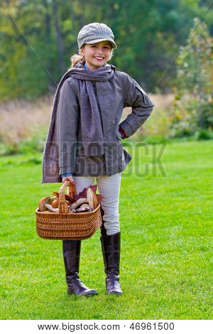 Mushrooms picking, season for mushrooms - lovely girl with basket of picked fresh edible mushrooms