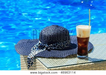 Ice coffee Fredo against blue clear water of the swimming pool with straw hat
