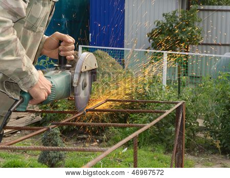 Angle Grinder Metal Sawing With Flashing Sparks Close Up And Repairman Hands Home Repair Garden Work