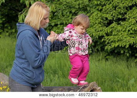 Baby walking on a tree trunk