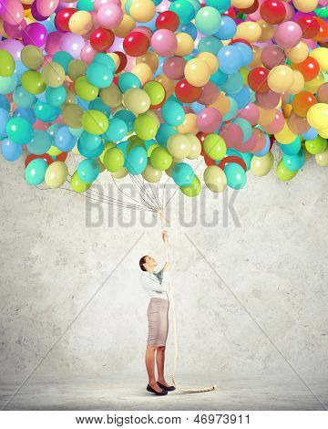 Image of young woman holding bunch of colorful balloons