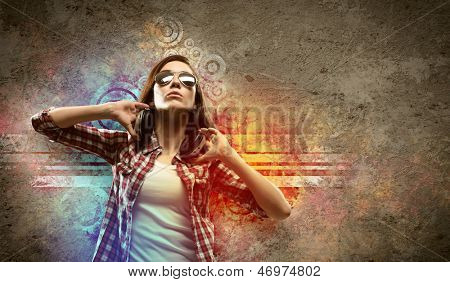 Image of young pretty woman with headphones dancing