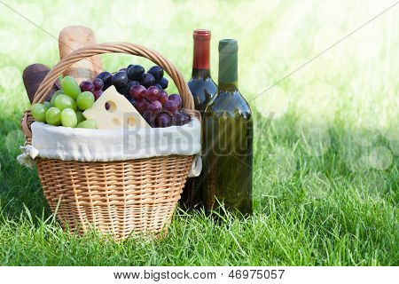 Outdoor picnic basket with bread, cheese and grape and wine bottles on lawn