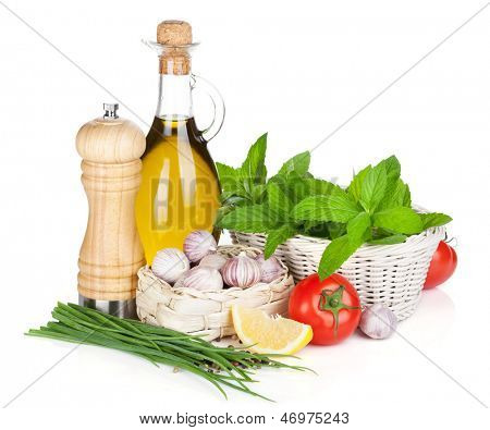 Fresh herbs, tomato, olive oil and pepper shaker. Isolated on white background