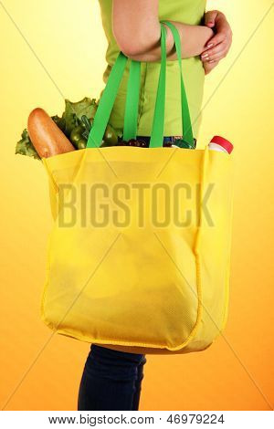 Girl with shopping bag on orange background