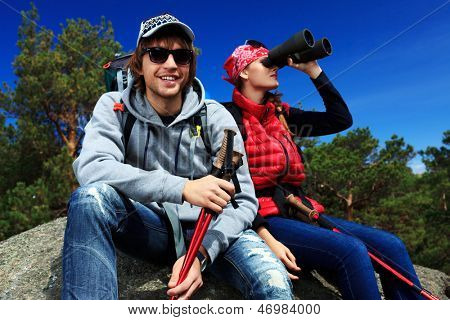 Couple of tourists are sitting at the top of a mountain and looking to the distance through the binocular.