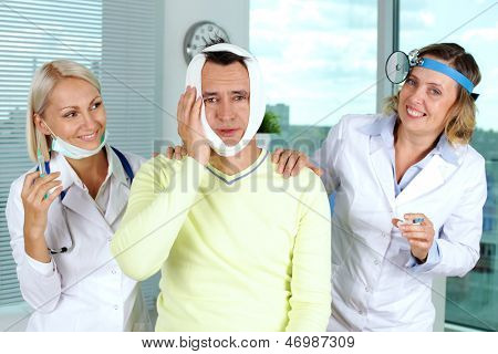 Portrait of two careful female doctors giving first aid to male patient with toothache in hospital
