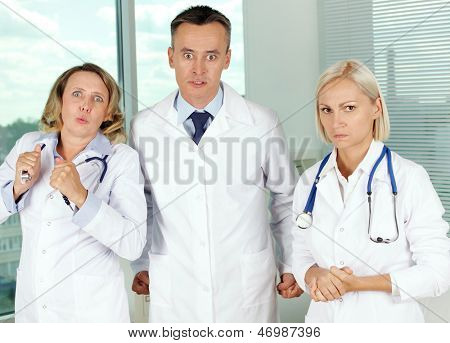 Three clinicians in white coats looking at camera with annoyed expression