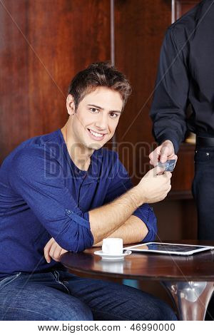 Young man in caf�?�?�?�© paying his coffee with a credit card
