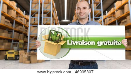 A man holding a Livraison gratuite board, meaning free delivery in French,  in a distribution warehouse