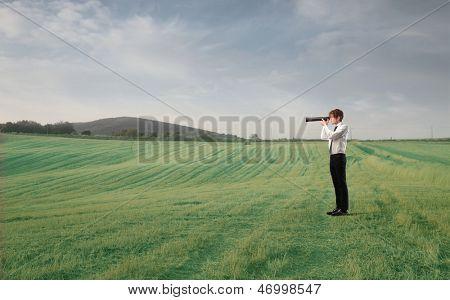 joven empresario con catalejo en el campo