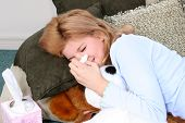 stock photo of flu shot  - Child on floor with pillows and tissue sneezing - JPG
