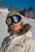 stock photo of skidder  - Snowboarder girl on snowy ski slopes wearing goggles cap and coat - JPG