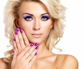 stock photo of fingernail  - Beautiful blond woman with beauty purple manicure and makeup of eyes - JPG