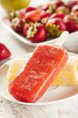 stock photo of popsicle  - Cold Organic Frozen Strawberry Fruit Popsicle with a stick - JPG