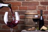 stock photo of wine cellar  - Glass of wine and some fruits bottle of wine cheese against a brick wall - JPG
