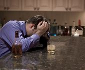 pic of alcohol abuse  - dark portrait of a man holding his head in despair and having an alcoholic drink - JPG
