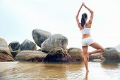 stock photo of enlightenment  - yoga beach woman doing pose at the ocean for zen health and peaceful lifestyle - JPG