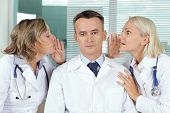 Portrait of calm male clinician between two gossiping women