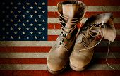 stock photo of boot  - Grunge US Army boots on sandy american flag background collage - JPG