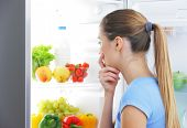 stock photo of refrigerator  - Young woman craving food choosing near refrigerator - JPG