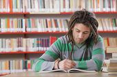 stock photo of dreadlock  - Young male student in the library studying - JPG