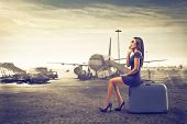 stock photo of trolley  - beautiful woman waits sitting on suitcase talking on the phone to start - JPG
