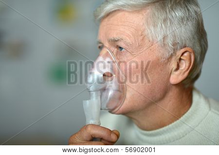 elder man making inhalation