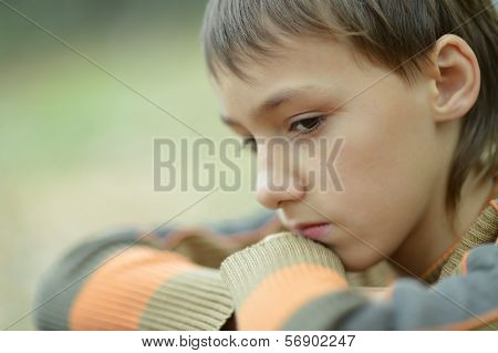sad little boy outdoors in autumn