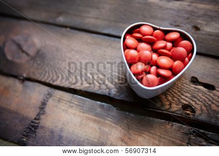 Red small candies in heart shaped box against wooden background