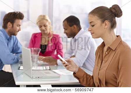 Young businesswoman sitting at a meeting, using mobilephone.