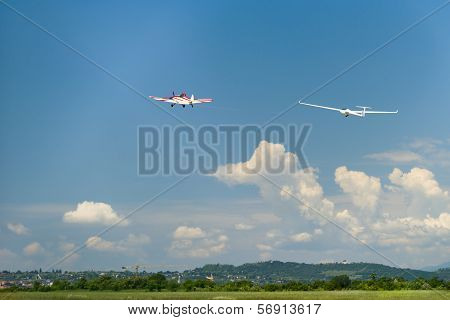 red motor airplane tows glider up in the air at blue cloudy sky