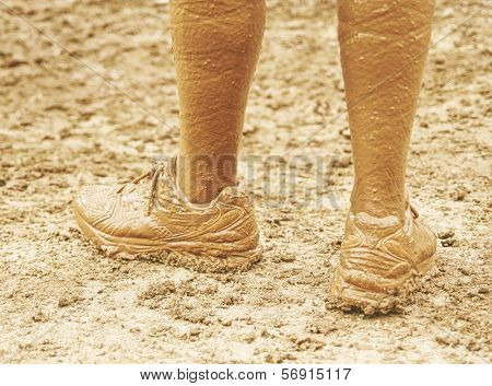 a pair of very muddy shoes and legs