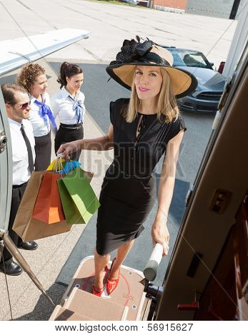 Full length portrait of confident rich woman carrying shopping bags while boarding private jet with pilot and airhostess standing by at airport terminal