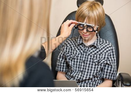 Female optician determining prescription values with trial frame for preadolescent boy in store