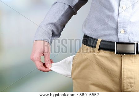 Man showing his empty pocket on bright background