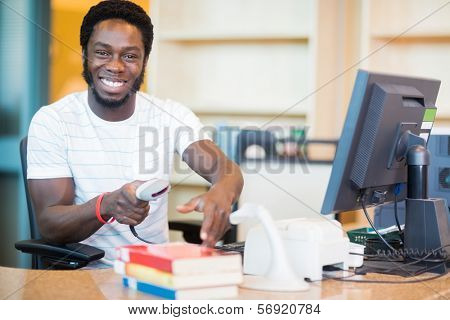Portrait of happy male librarian scanning books at desk in library
