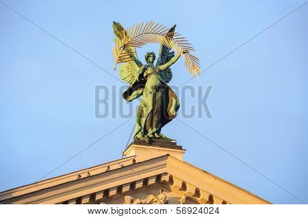 Statue at the roof of theater in Lviv, Ukraine, in rays of sunset.