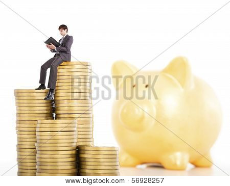 Young Man Counting Coin In Poggy Bank