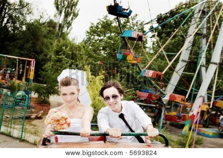 Bride And Groom On Rollercoaster With Ferris Wheel