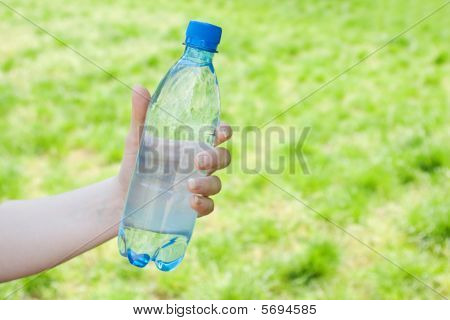 Hand Offering Bottle Of Water