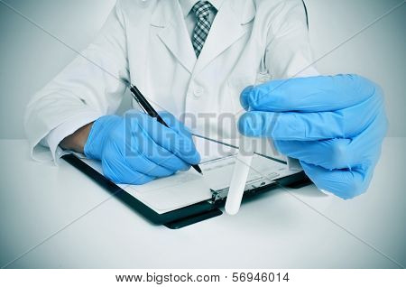 a man wearing white coat and blue medical gloves holding a semen sample in his hand