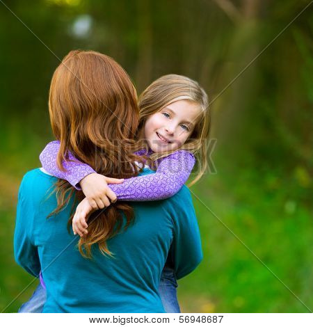 Mum holding daughter kid girl in her arms rear view smiling in outdoor