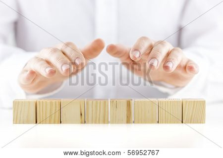 Man Holding Protective Hands Above Eight Wooden Cubes
