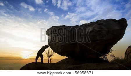 Man pushing a boulder on a mountain