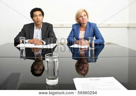 Two managers, mimicking body language and playing a psychological game during a stern job - or appraisal - interview