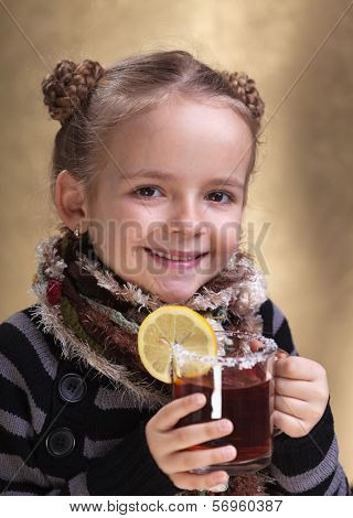 Smiling little girl fighting flu with traditional recipes- a nice hot cup of tea