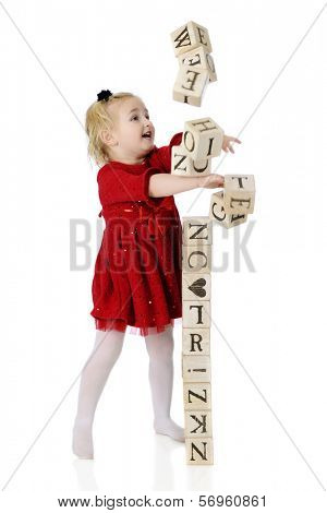 A young preschool girl knocking down the block tower she's built.  Motion blur on flying blocks.  On a white background.