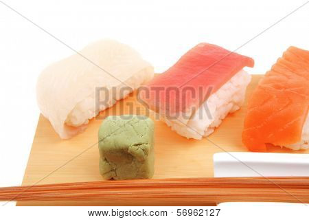 Japanese Cuisine - Set of Tuna (maguro) Salmon (sake) and Eel (unagi) Nigiri Sushi  with Wasabi on wooden plate isolated over white background