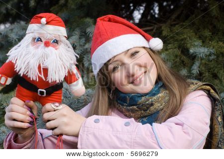 Girl Smiling Holding Santa Doll